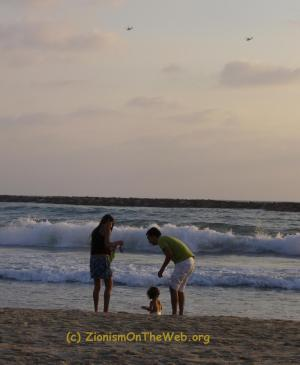A family at the beach in Israel, note the helicopters in the sky... they're need to pretect ordinary people's safty as they do ordinary things like take a day out at the Tel-Aviv beach